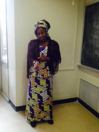 A student wearing a long Hausa-style purple and gold dress with a matching headtie, purple veil, and bangles