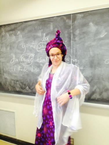 A student wearing a long Hausa-style purple dress with a matching headtie, white veil, and bangles