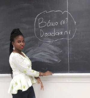 Omotola Okunlola standing in front of a blackboard