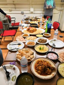 A large communal Arabic meal spread across a table at a Baytunaa event