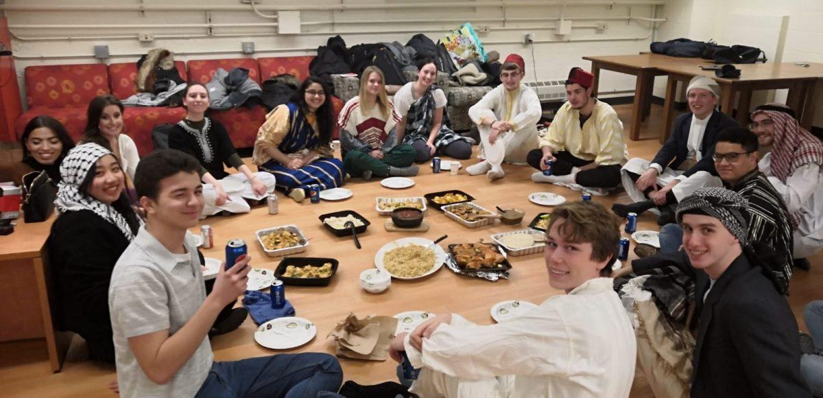 Baytunaa residents sitting in a circle enjoying an Arabic meal