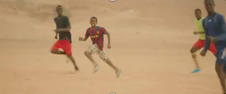 Four African boys playing soccer in the sand, one wearing Lionel Messi's jersey